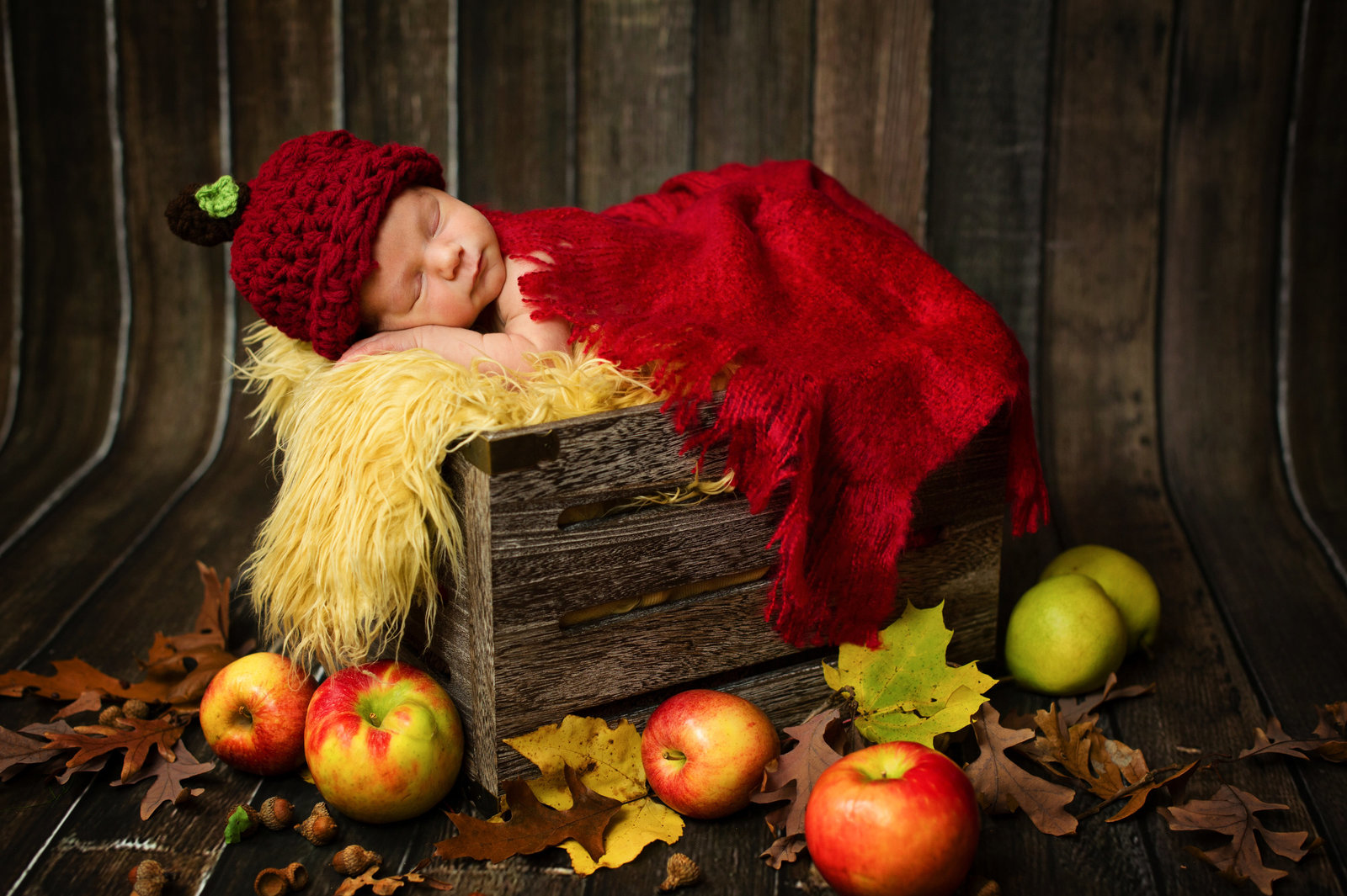 newborn baby sleeping in rustic box with crochet apple hat, apples and brown wood background