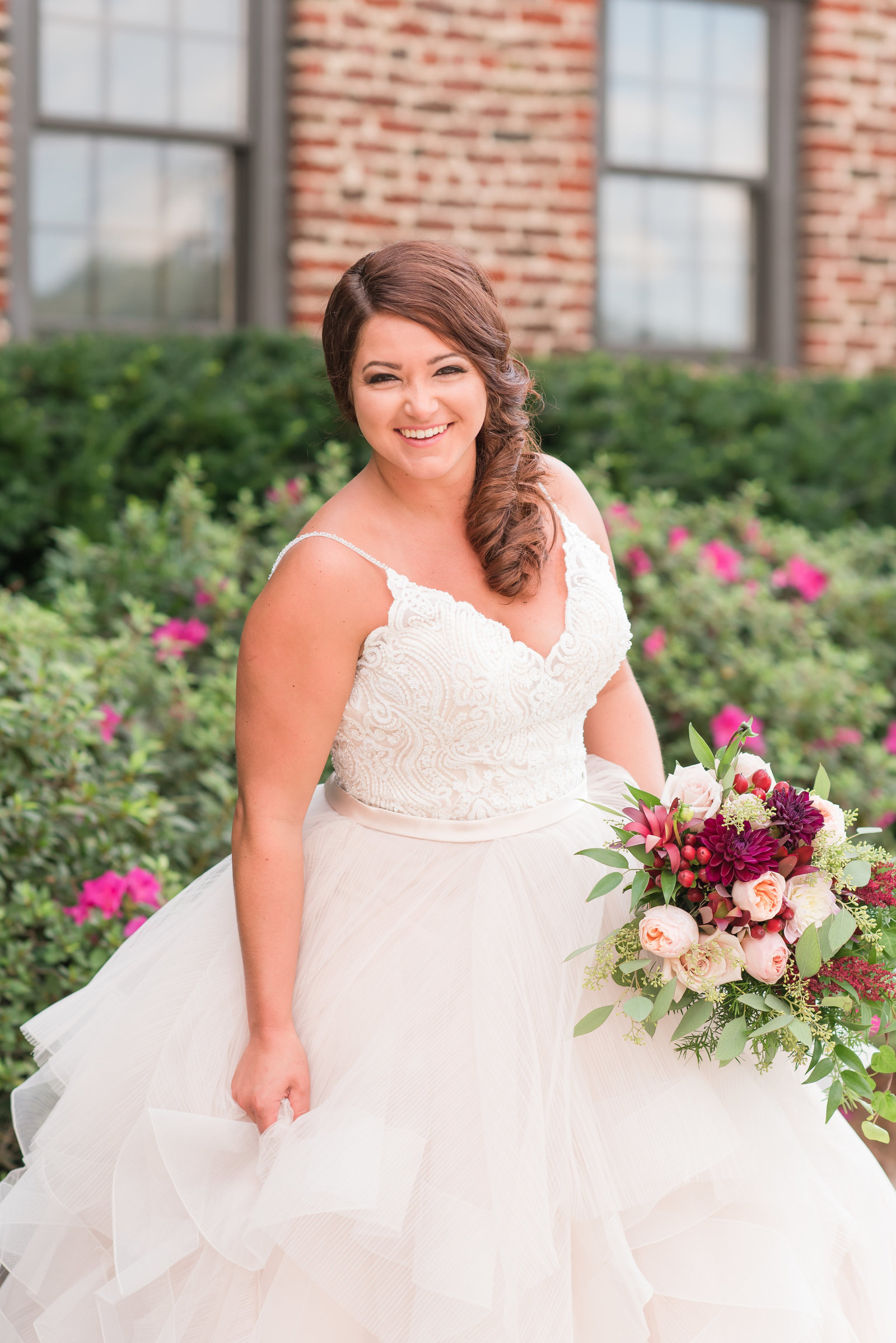 a bride in a champagne  colored dress holding a  pink and red bridal bouquet standing in front of purple flowers smiling at the camera at Sedgefield Country Club