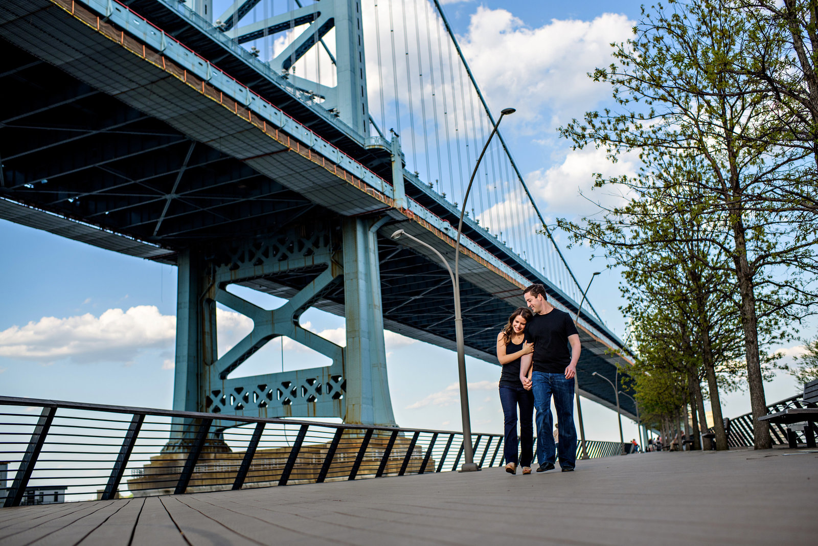 A happy couple walk along race street pier with ben franklin bridge behind them.