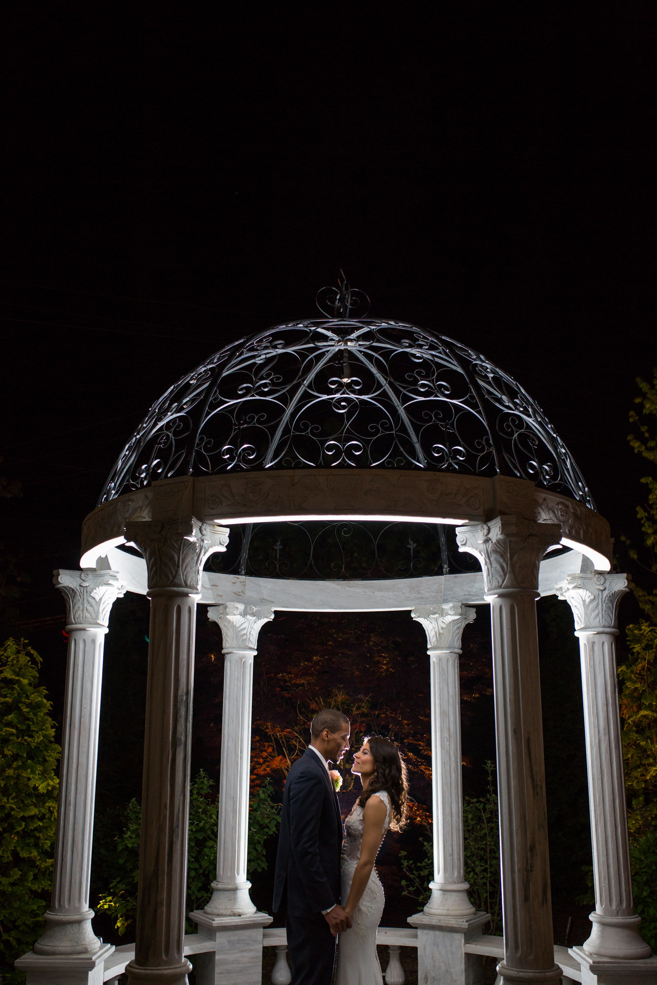 bride and groom under a gazebo at night at the waterfall in claymont delaware