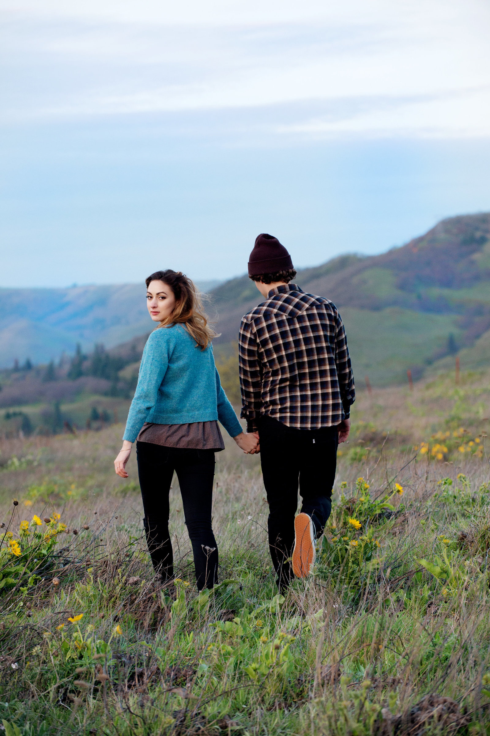 a girl looks over her shoulder as she walks hand in hand with her fiance at rowena crest