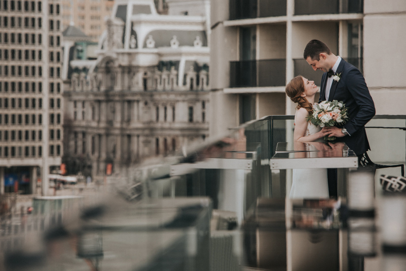 rooftop portrait of the bride and groom overlooking philadelphia city hall at the logan hotel in philadelphia pa