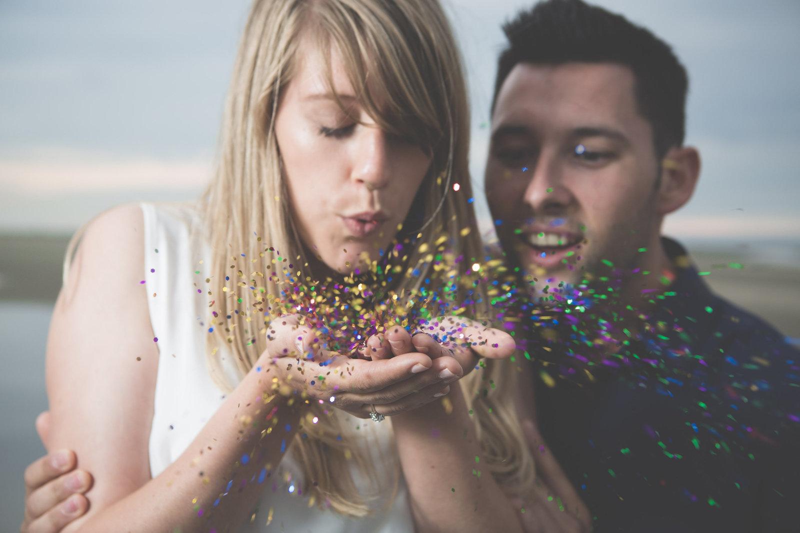 strand kust verloving shoot Emma en Wouter blazen confetti foto