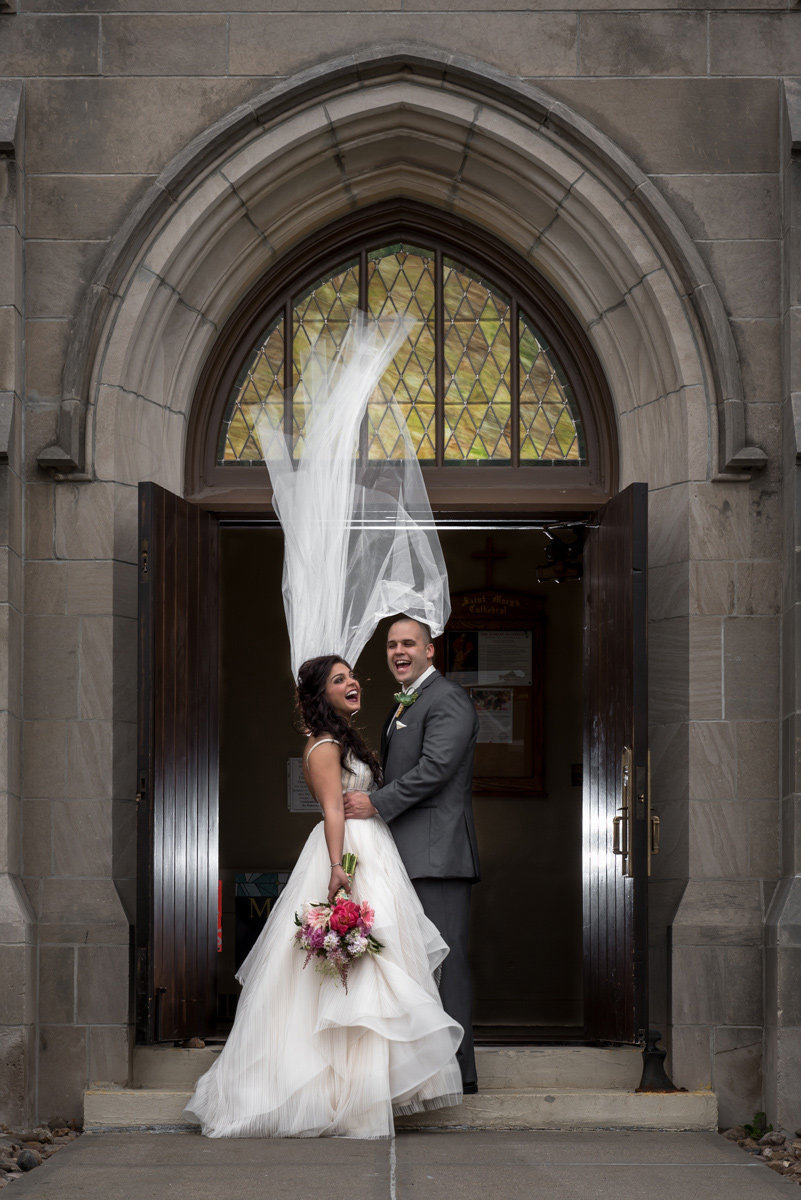 bride and groom laughing blowing veil grand island nebraska
