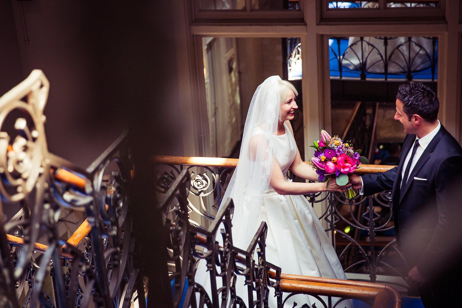 Bruid en bruidegom ontmoeten elkaar op de trappen van hotel New York in Rotterdam. Bruidegom geeft het trouwboeket aan zijn bruid. Copyright Nanda Zee-Fritse | FOTOZEE