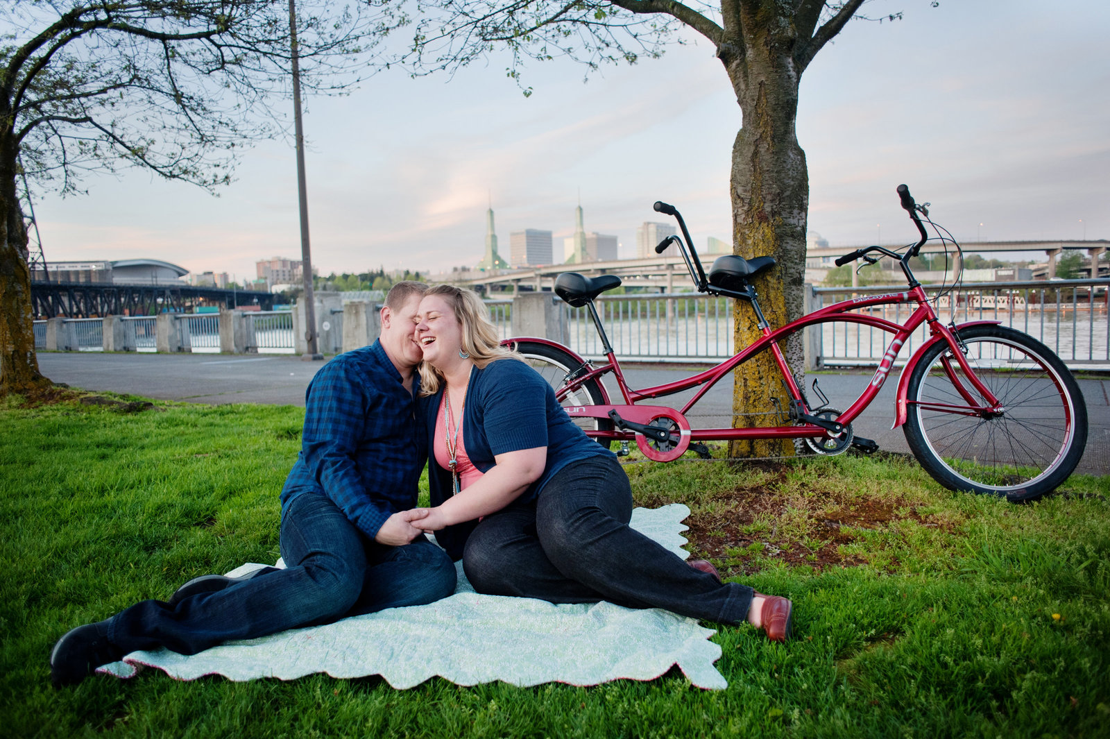 a girl and guy sit on a blanket on the grass with a tandem bike in the background