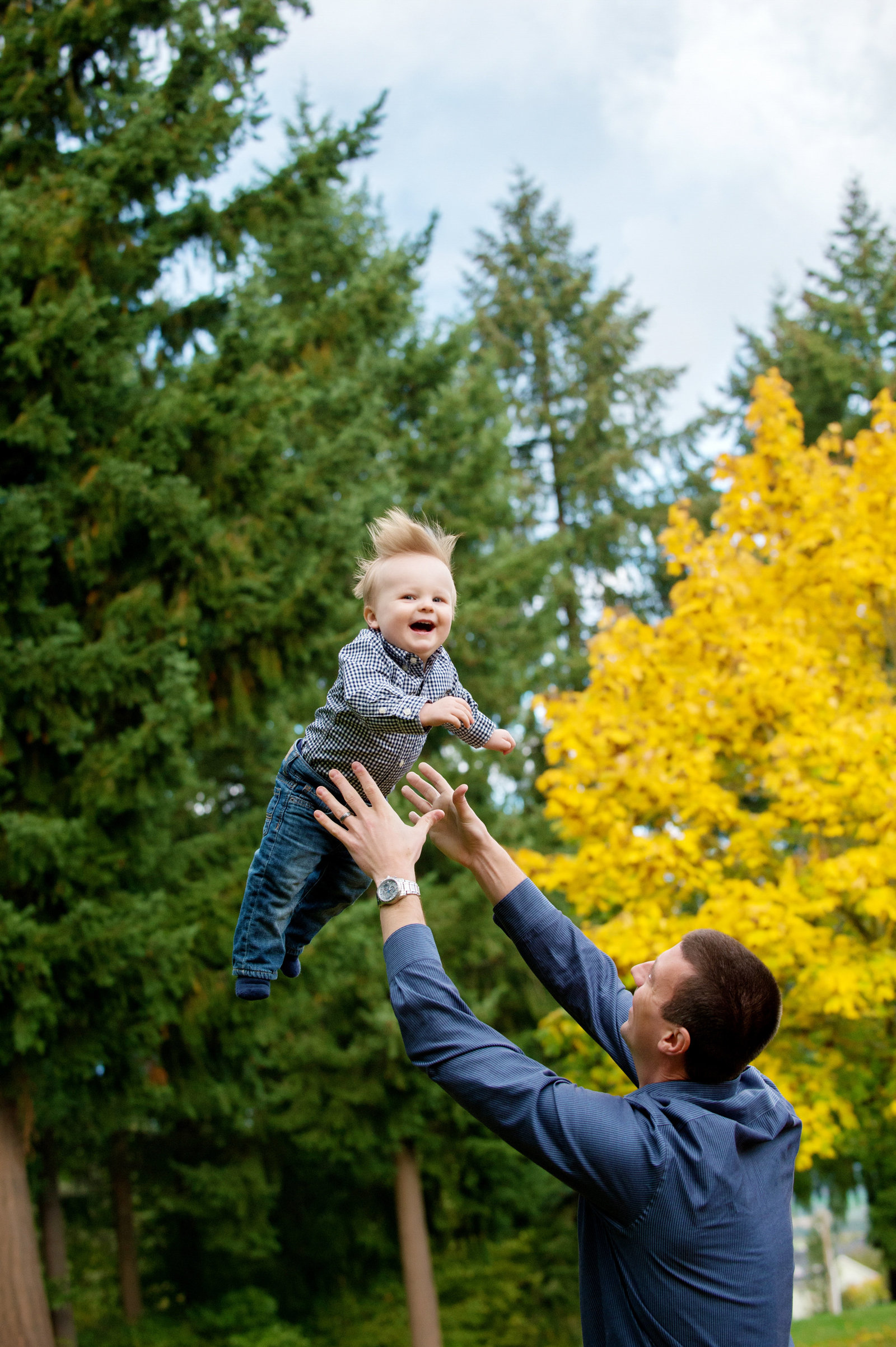 a dad throws his laughing son into the air