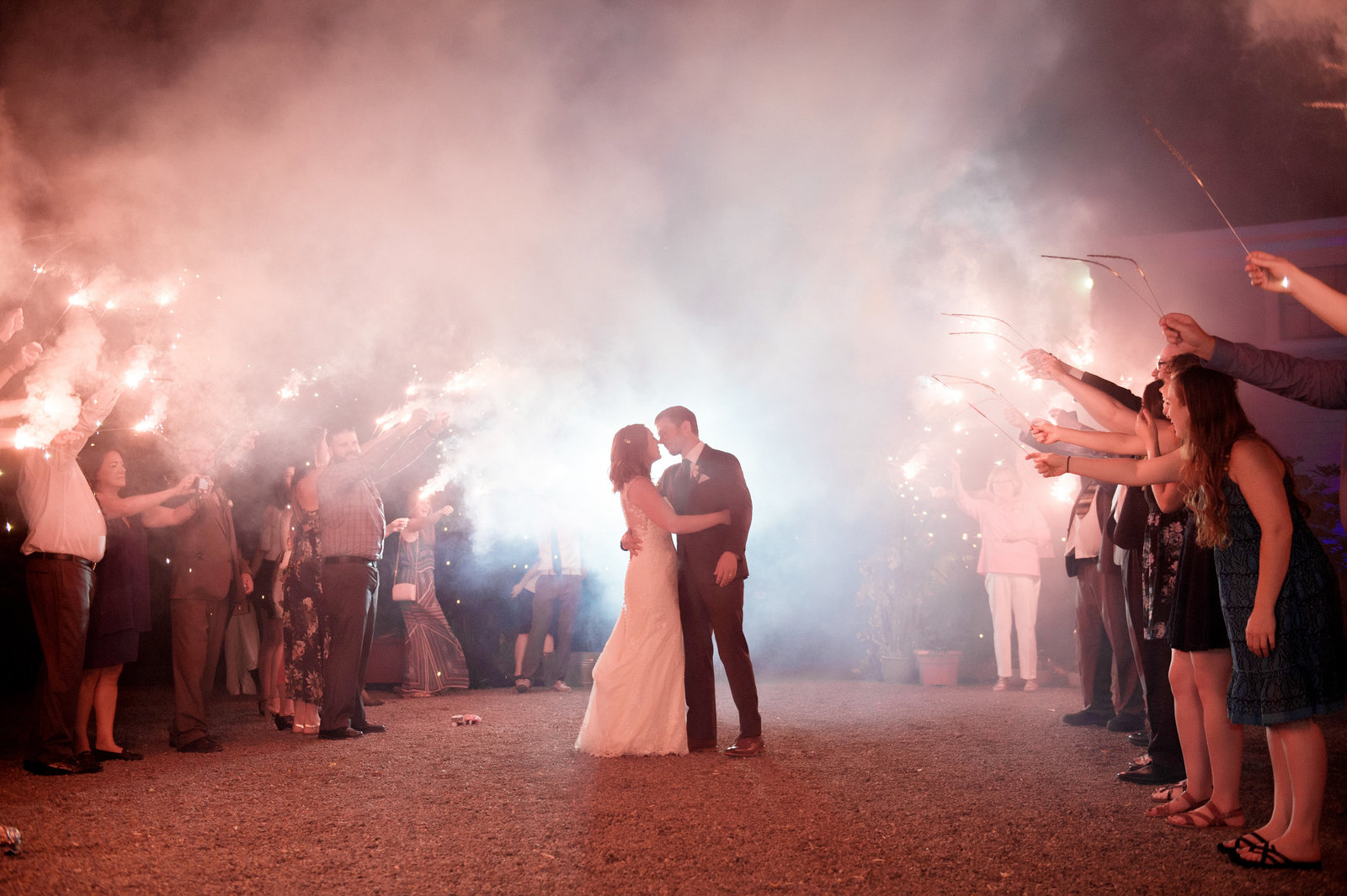 wedding kiss under smoky sparkler exit at ainsworth house