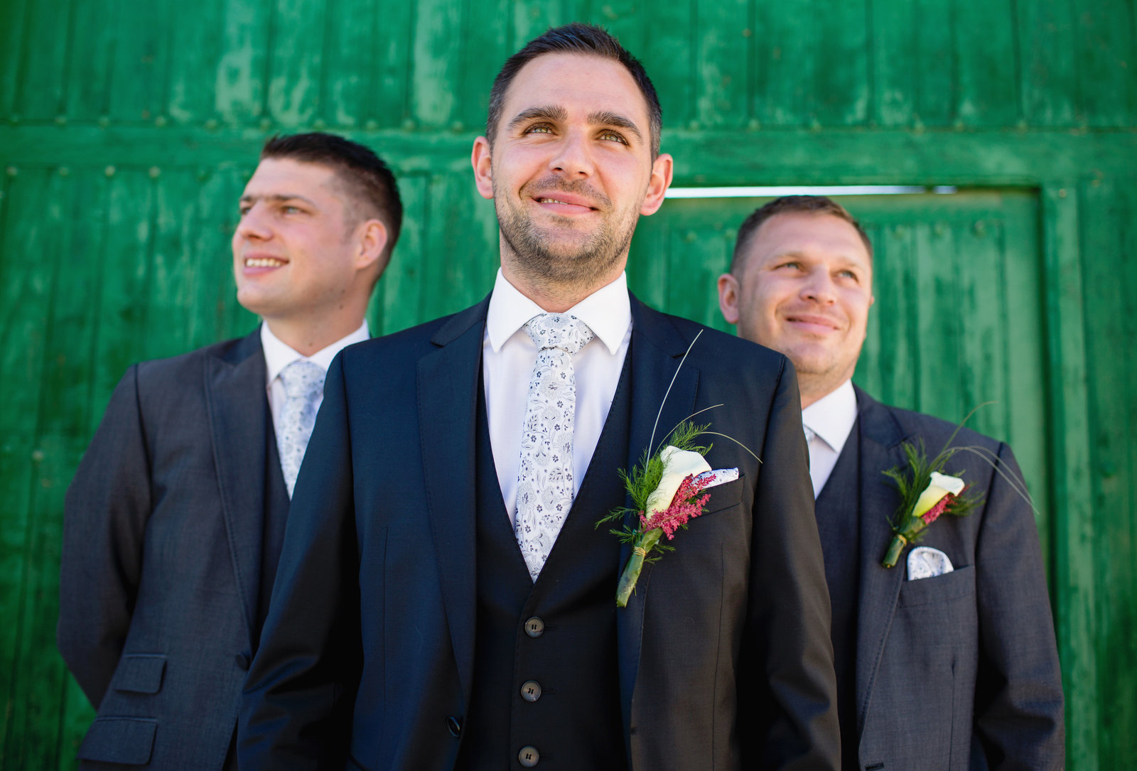 The Groom poses with his best man and usher behind him in front of a green wooden barn for a pre wedding photo taken by Motiejus wedding photographer while second shooting for Adorlee at this Spanish destination wedding.