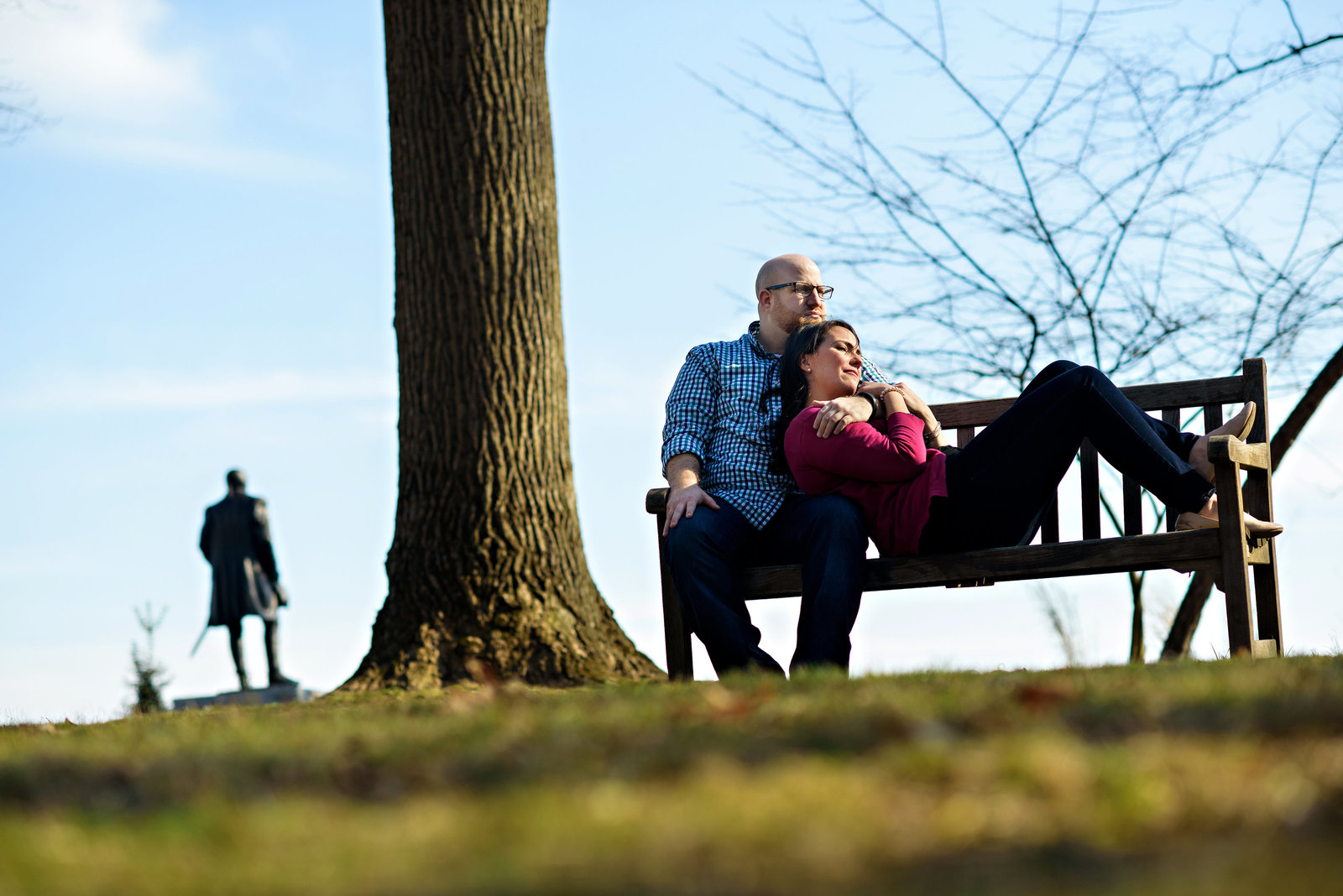 A couple lay on a bench in valley forge state park.