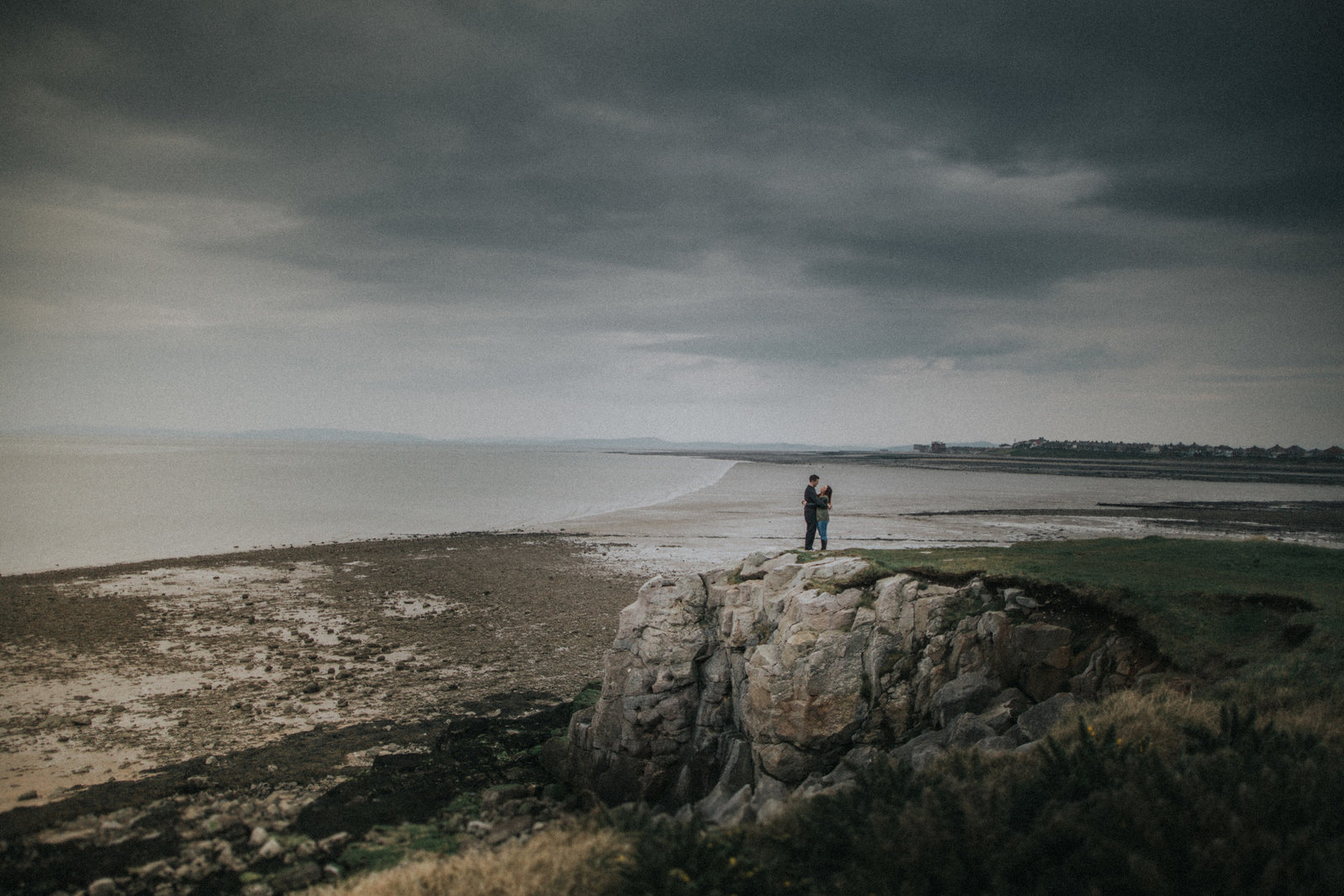 Engaged couple stood with backdrop of Morecambe Bay by Lancaster Wedding Photographer Jono Symonds