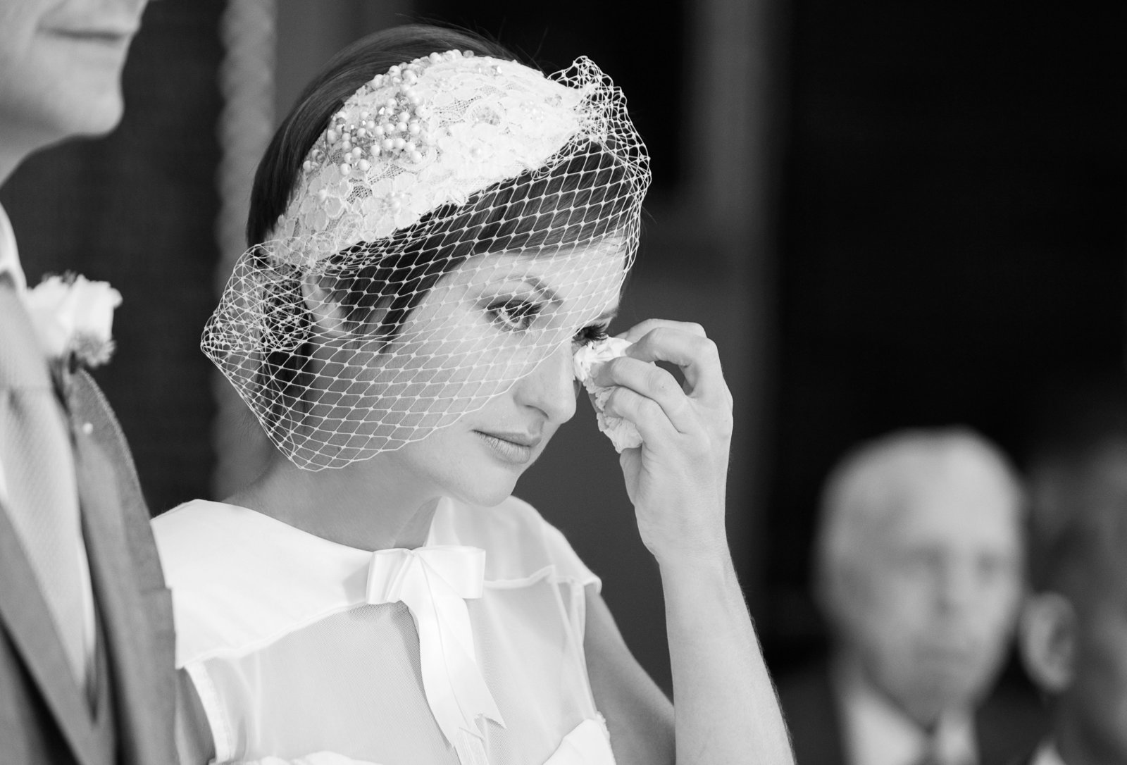 Beautiful bride catches a tear with her tissue while getting emotional at her wedding ceremony in Chichester in this black and white photo by Adorlee