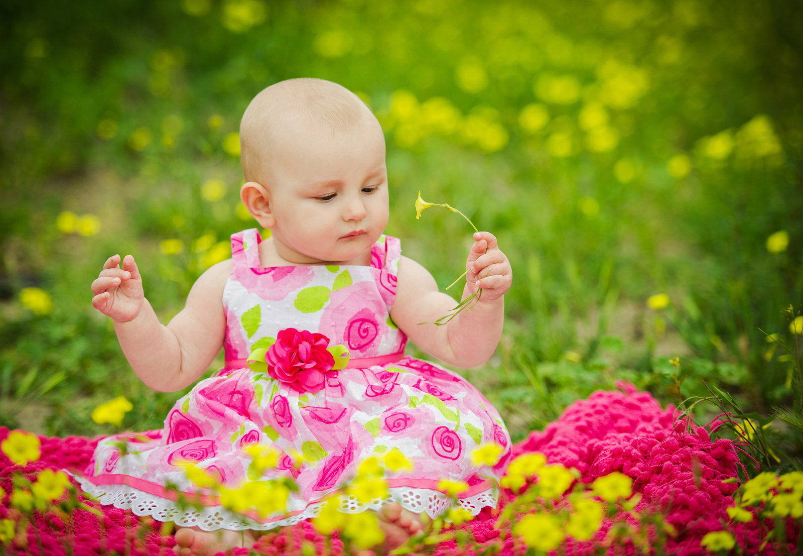 baby in floral dress holding flower