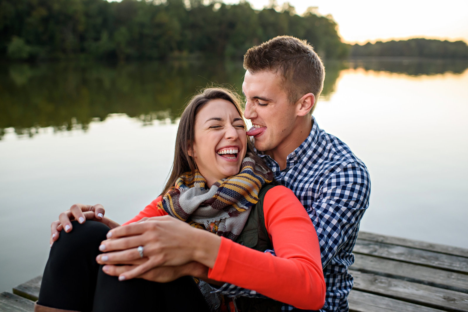A man licks his fiance's cheek while sitting on a dock floating on a lake in Delaware.