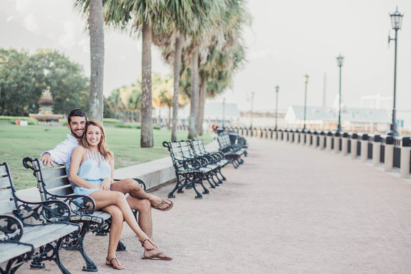 Engaged couple sits on a bench, watching the ocean, Waterfront Park, Charleston, South Carolina