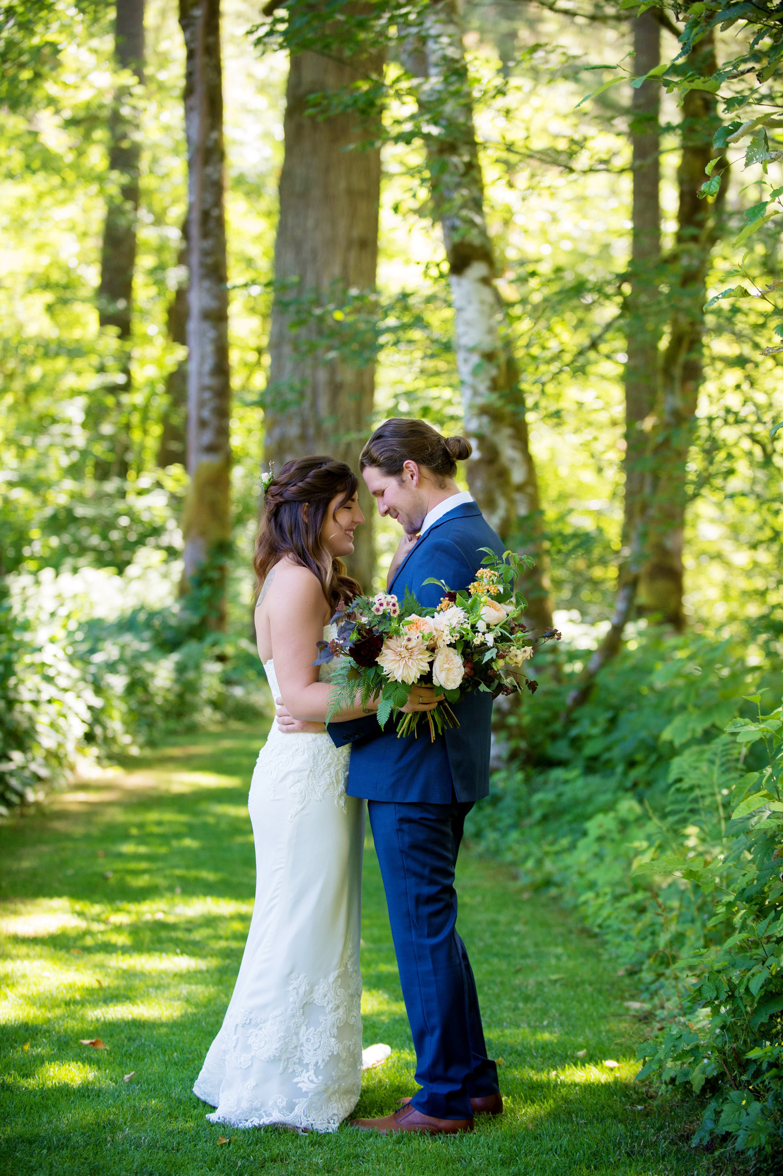 bride and groom embrace in forest at bridal veil lakes