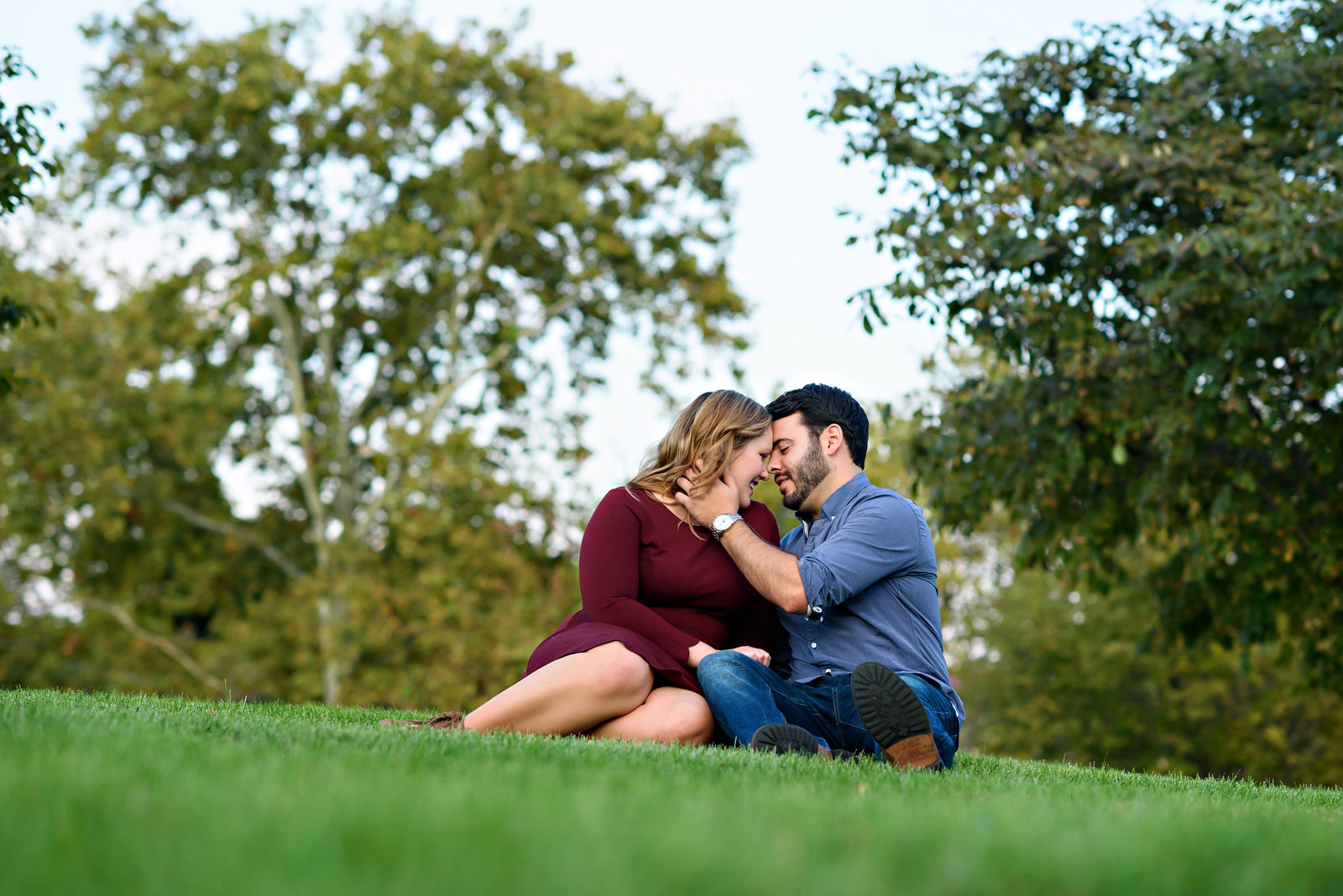 A man brings his fiance in for a kiss while sitting on the grass at the Philadelphia Museum of Art.