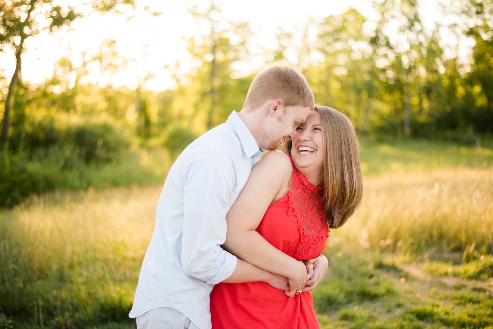joyful-future-bride-and-groom-standing-in-a-field-during-their-engagement-session-at-Cox-Arboretum