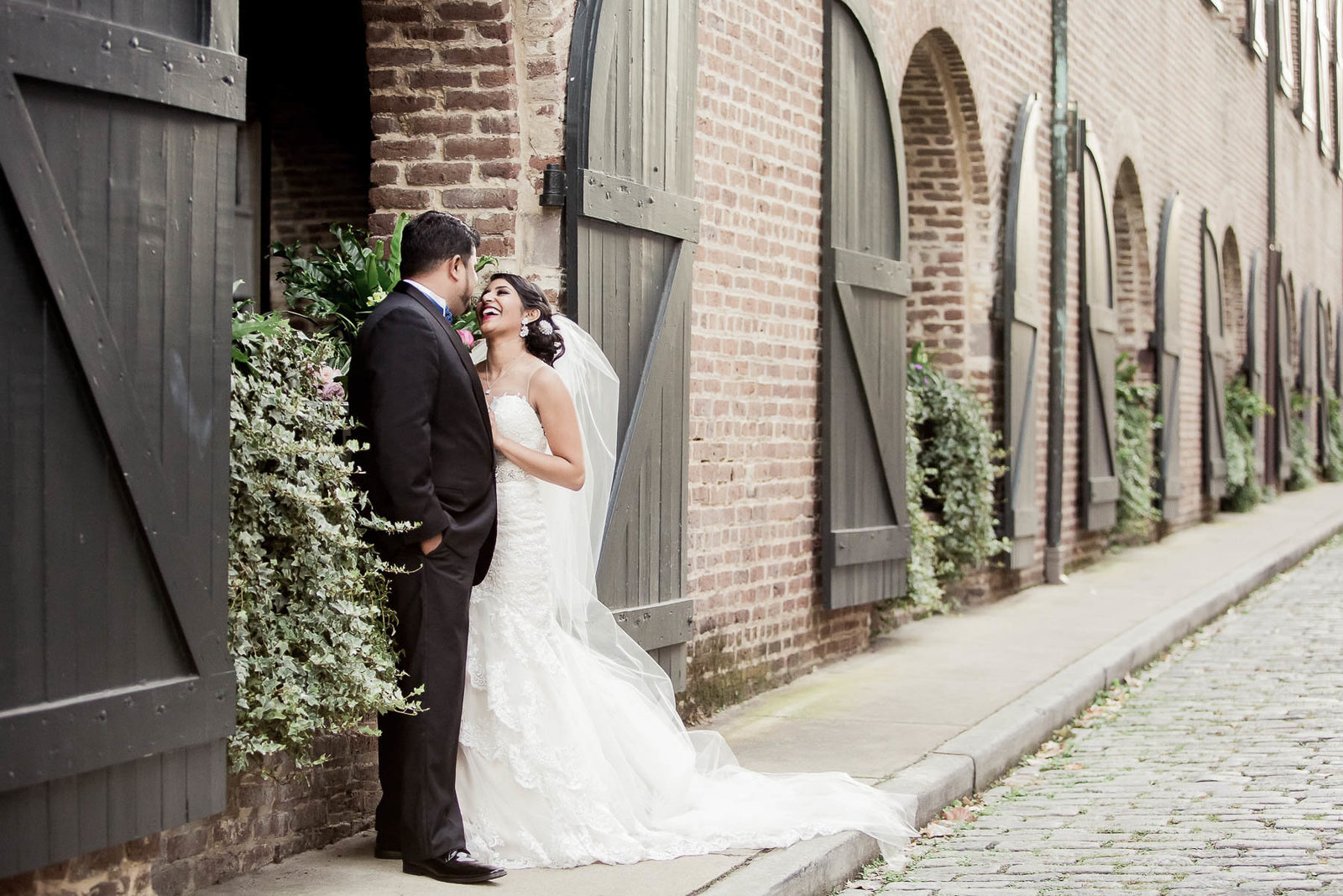 Bride and groom stand by stable doors, French Quarter, South Carolina