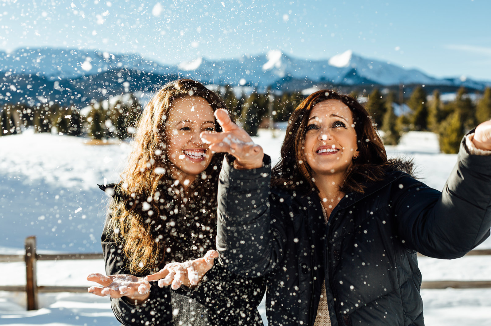 Mother and daughter throwing snow in the air and laughing together in Colorado
