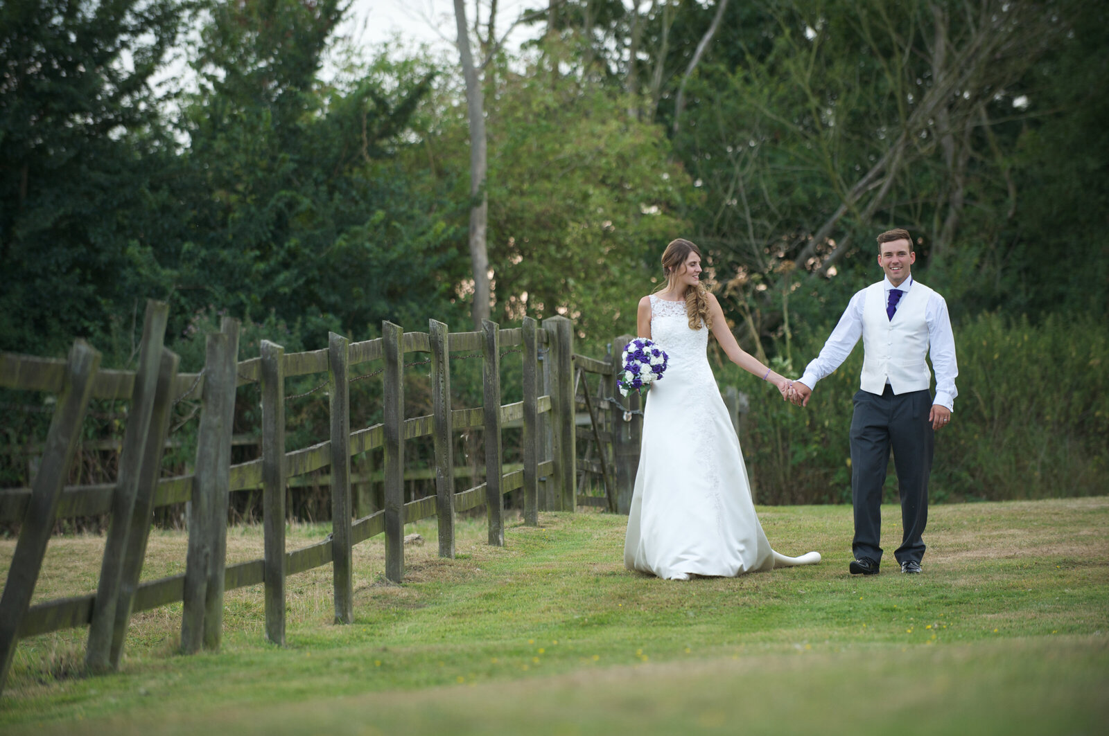 Bride and groom next to old fence