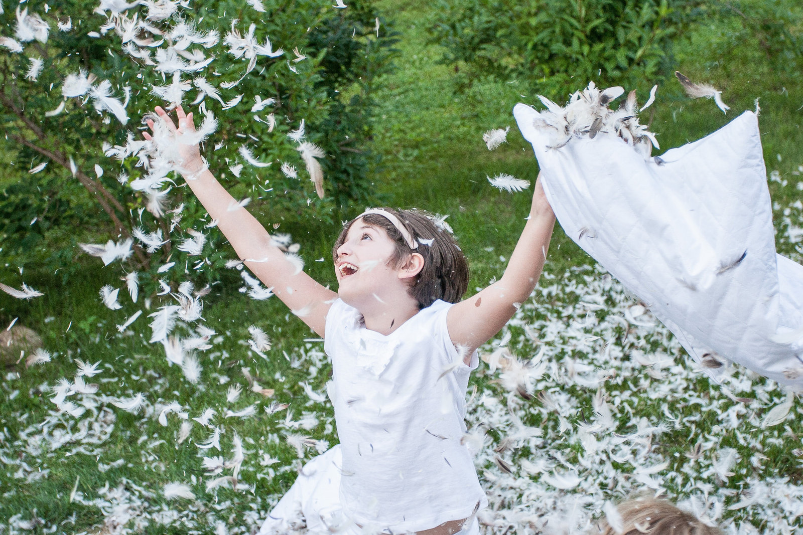Fun feather pillow fight with best friends tweens kids by Hudson Valley children's photographer in Cornwall NY