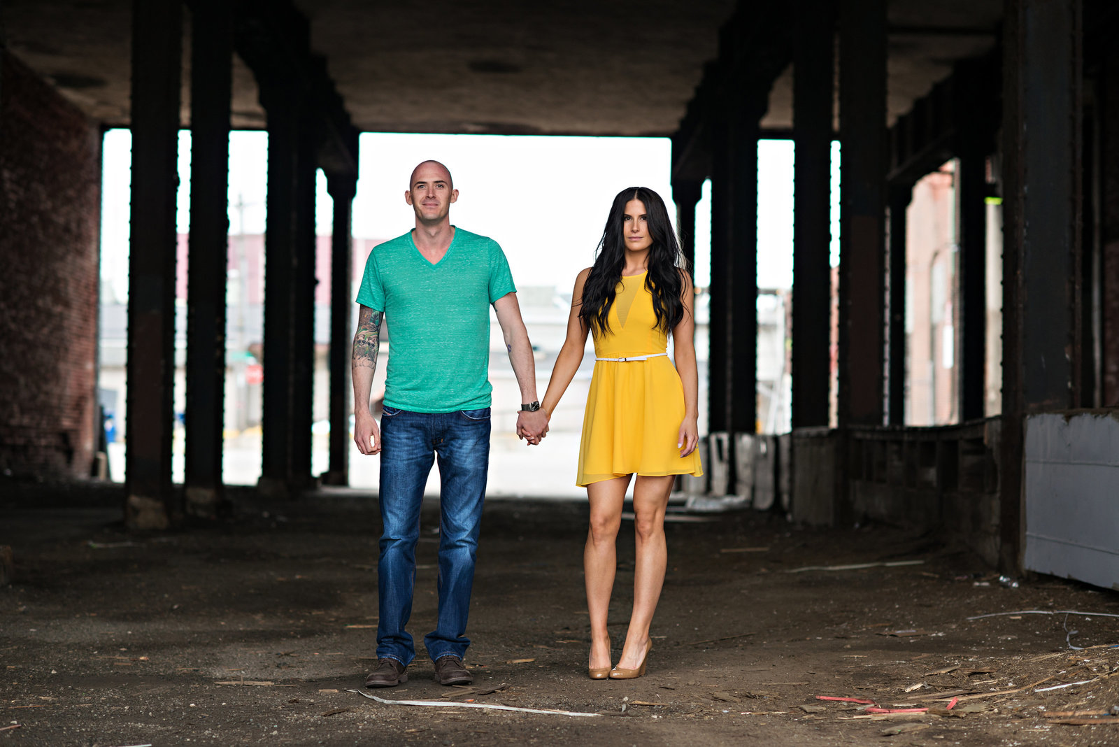 A sexy couple hold hands in the industrial part of old city philadelphia.