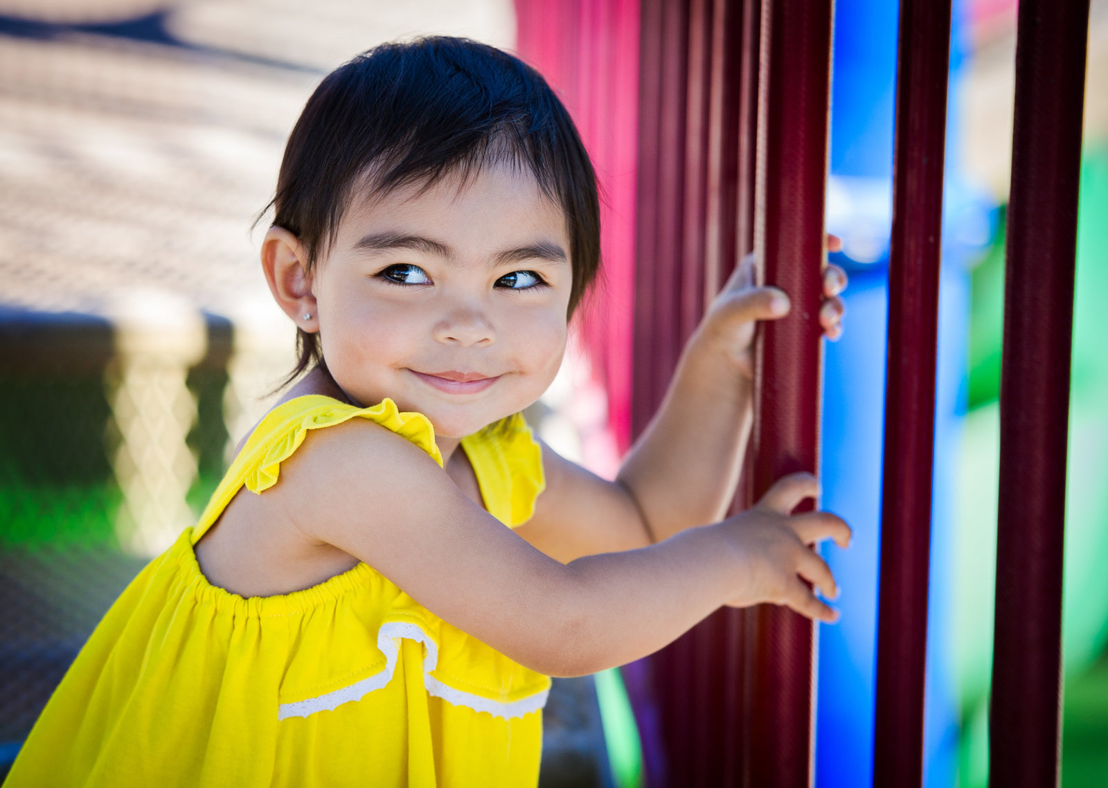 mischievous little girl in bright yellow dress at playground