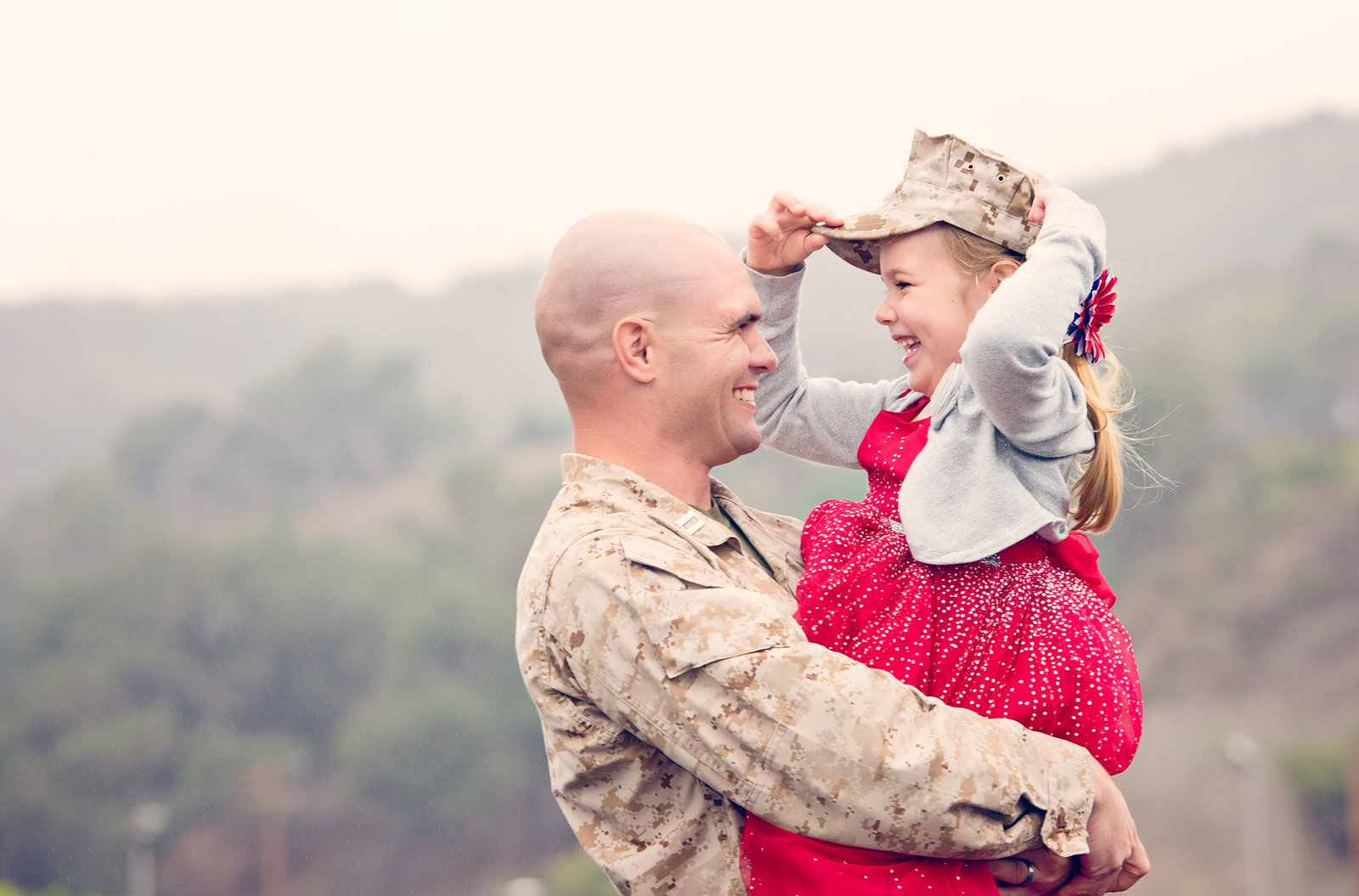 Homecoming photograph of deployed marine holding daughter wearing his uniform hat by inGRACE photography