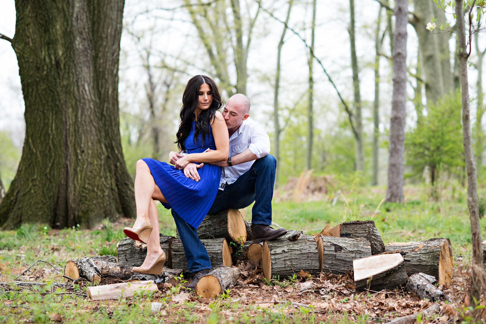 A bride to be sits on her fiance's lap on top of chopped logs in the woods.