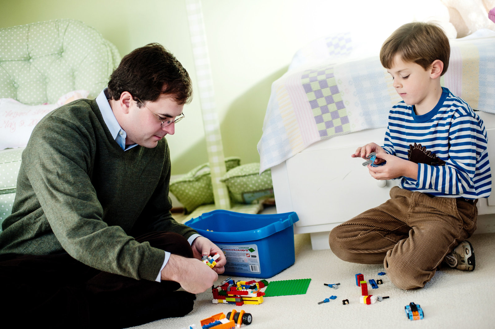 a dad helps his son build legos in his bedroom