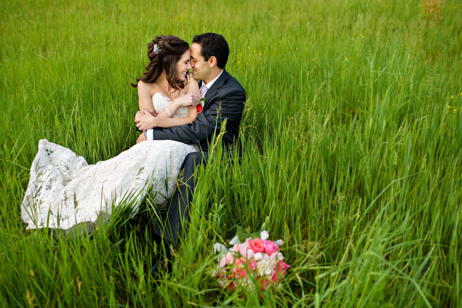 A couple lay in the tall grass after getting married at Holly Hedge Estate in bucks county.