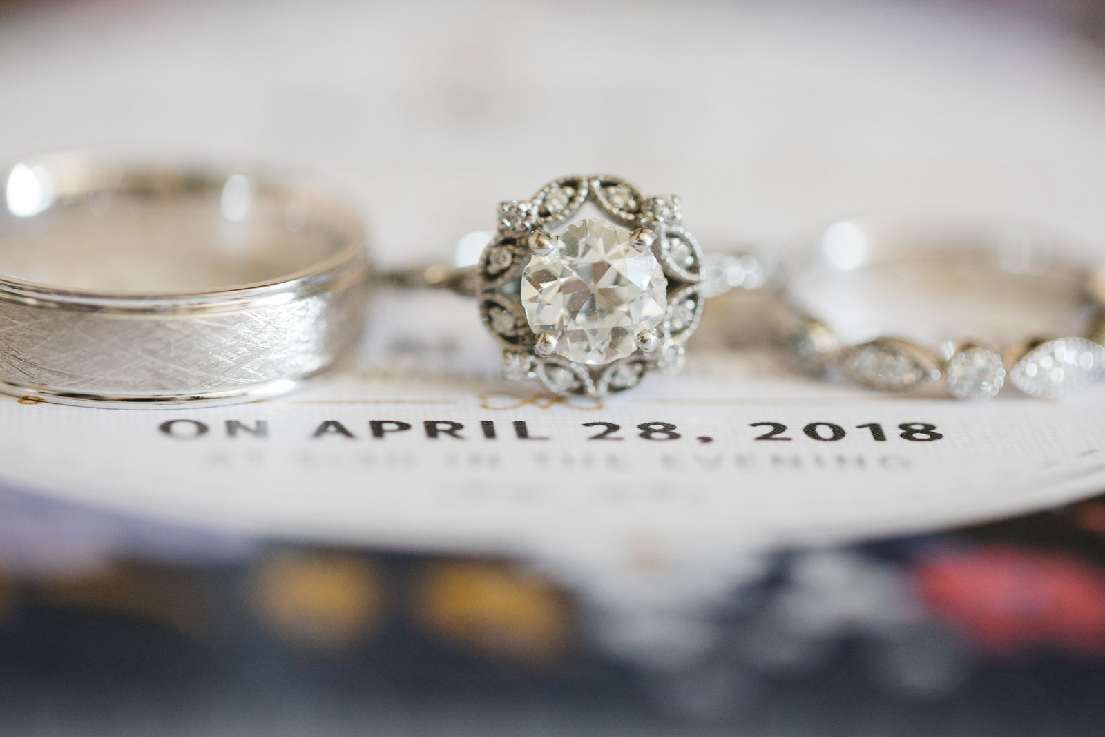 This close up of Joey's grandmother's diamond set in her wedding band with their invitation to show their wedding date of April 28, 2018