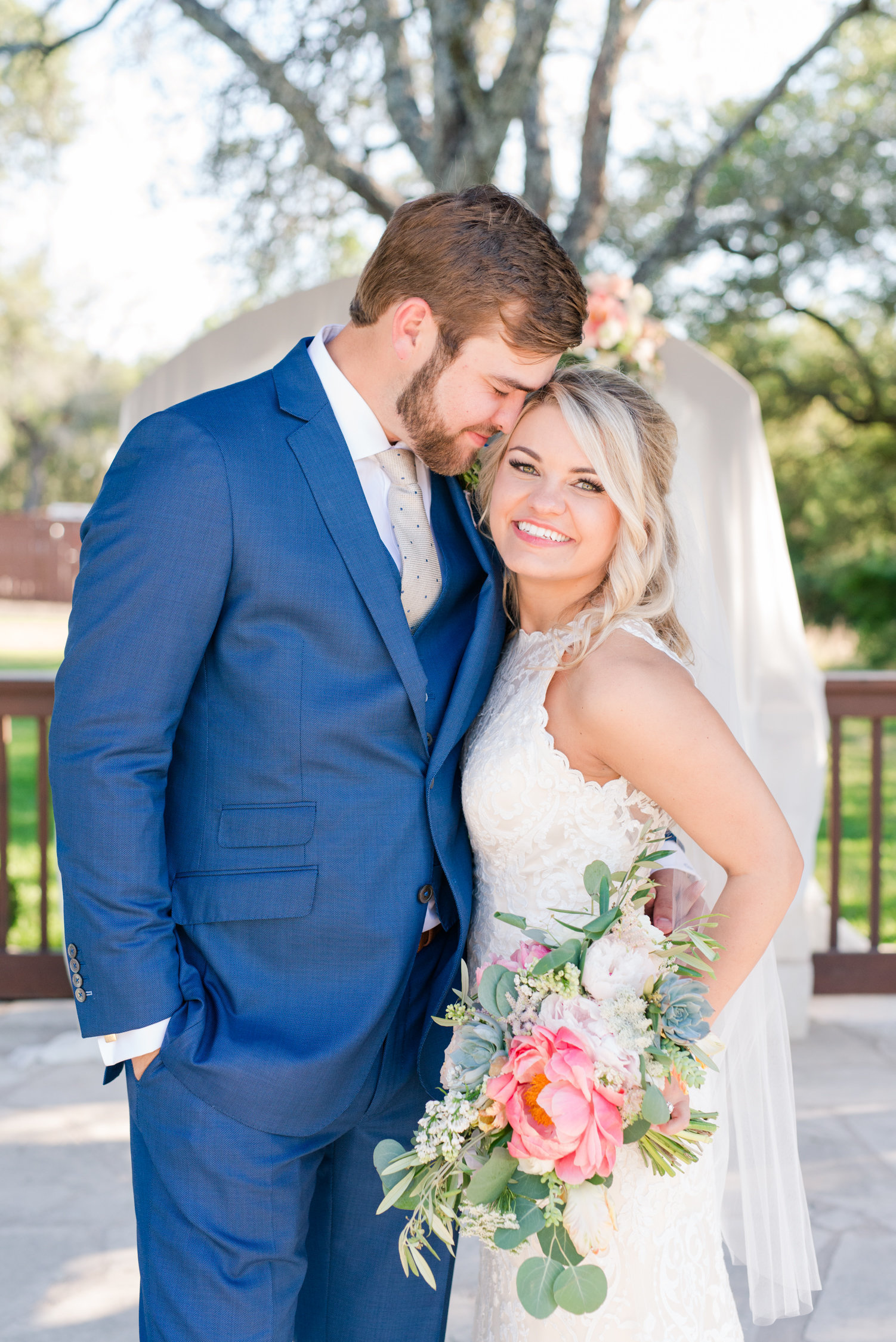 Wedding Photographer for The Springs in Georgetown: Bride smiles at camera holding pink bouquet as groom kisses her temple