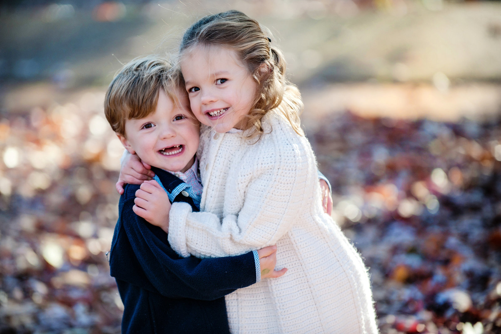 a brother and sister embrace at latta park in the fall