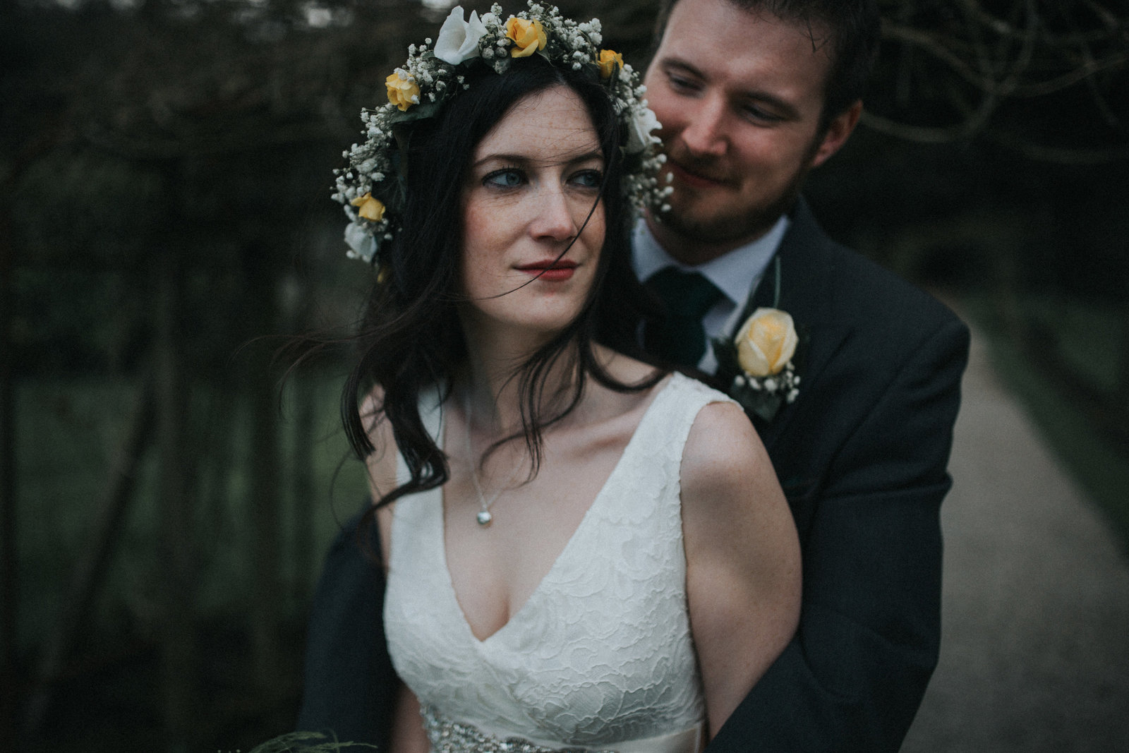 Groom with arms wrapped around his bride who is wearing a floral headpiece looking of camera by Lancashire Wedding Photographer Jono Symonds