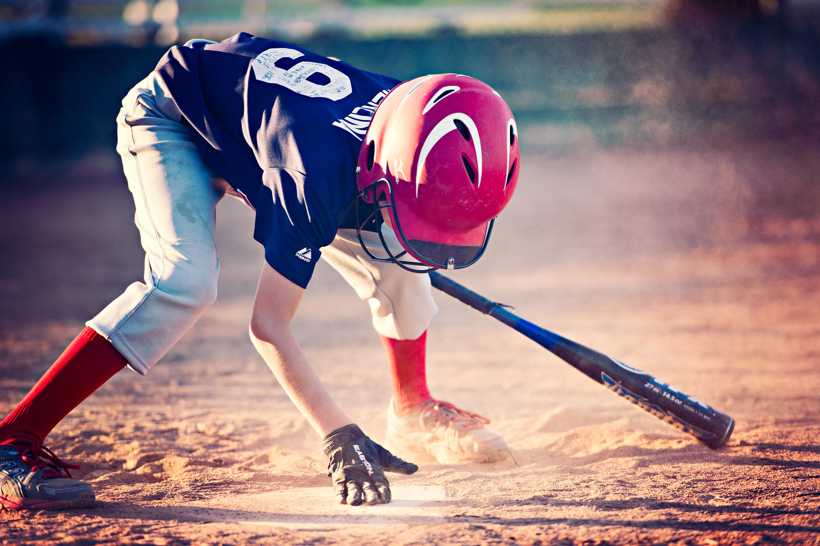 boy playing baseball dusting off home plate with bat