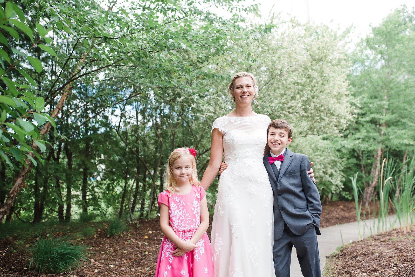 bride with son and daughter, wedding ceremony in a garden
