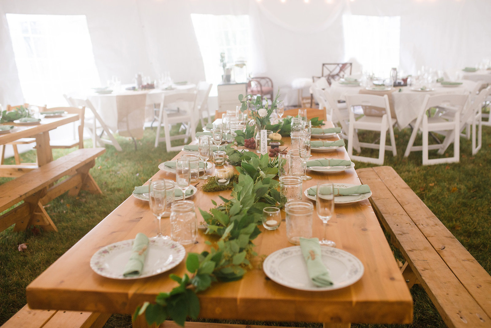 farm table with green garland, eucalyptus greenery, tent wedding