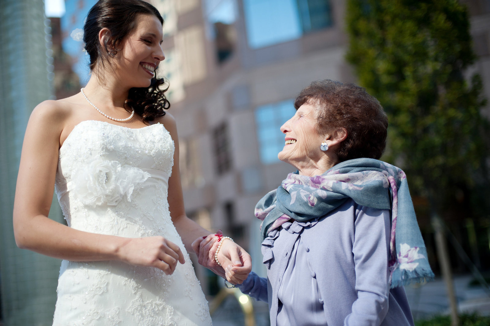 short grandma looks lovingly up at bride