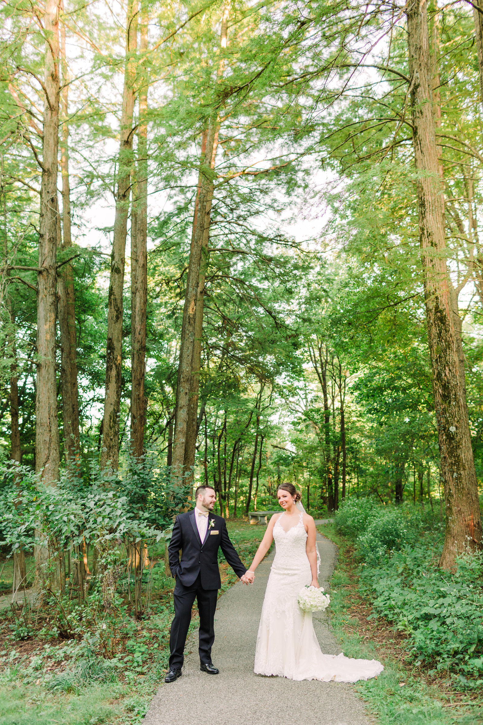 Portrait of Bride and Groom, Courtney and Dan, on a path surrounded by trees at the Gardens of SIUe by Jackelynn Noel Photography