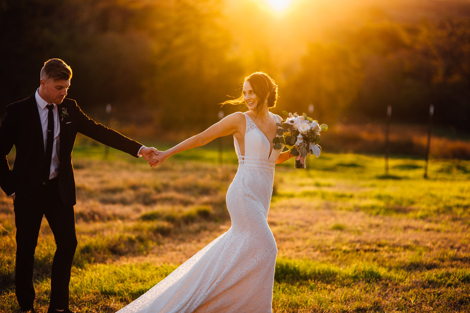 Bride leading groom through field during golden hour