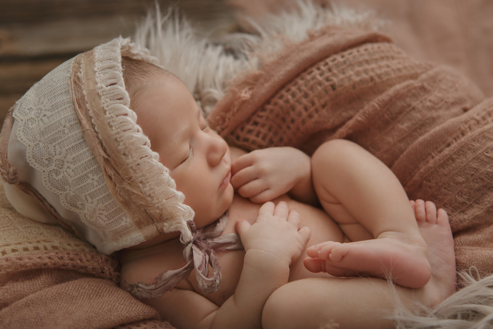 Brewster NY newborn baby girl sleeping curled up in a fur and fabric lined basket wearing a vintage bonnet on a barn wood floor by Hudson Valley professional baby photographer Cornwall NY photo studio