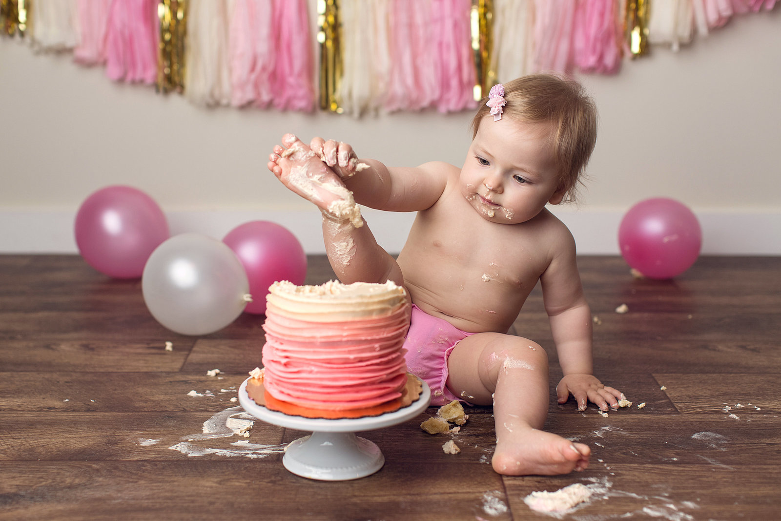 one year old girl smashing cake with feet