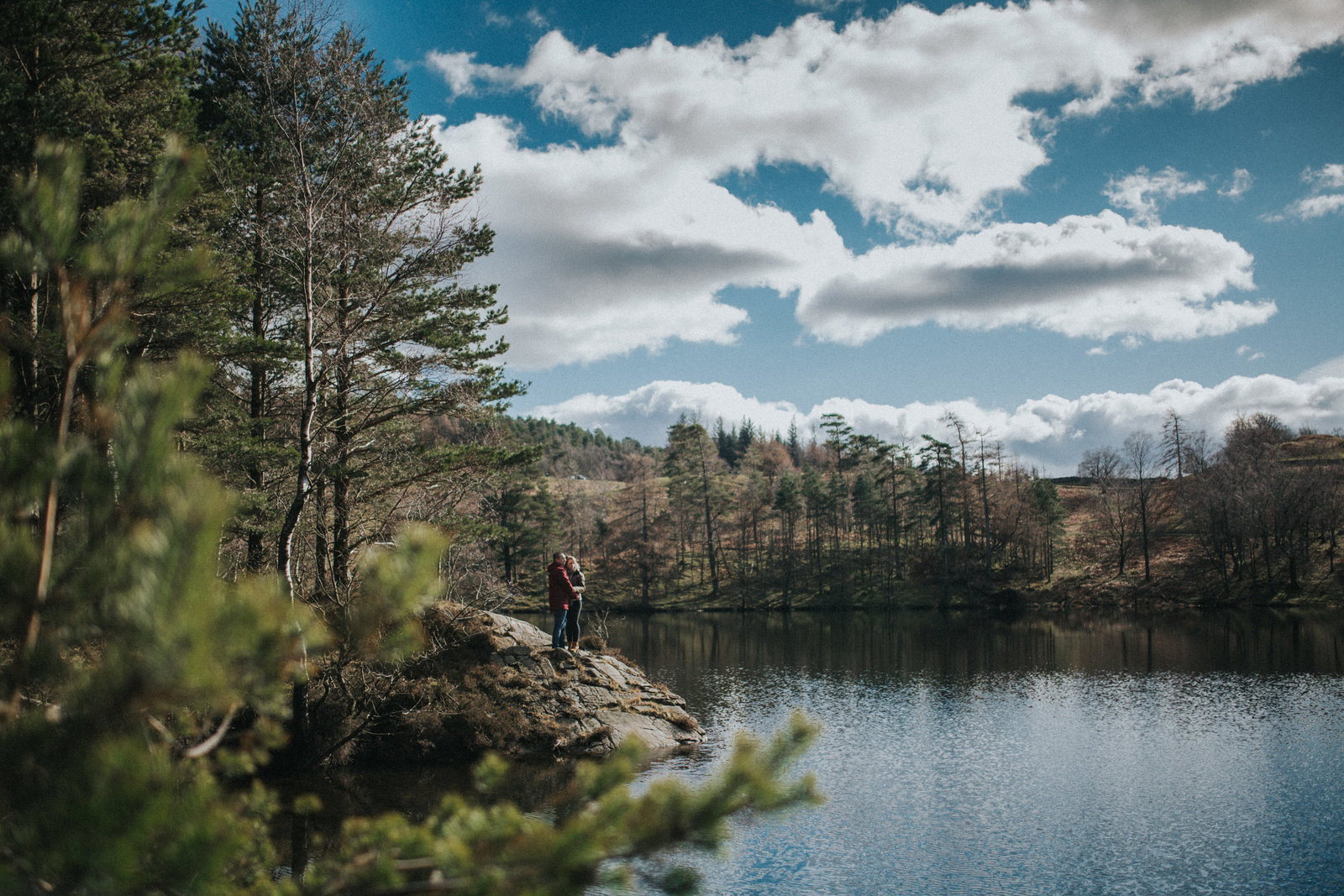 Pre-wedding shoot showing couple stood on the edge of a lake in The Lake District,  by Cumbria Wedding Photographer Jono Symonds