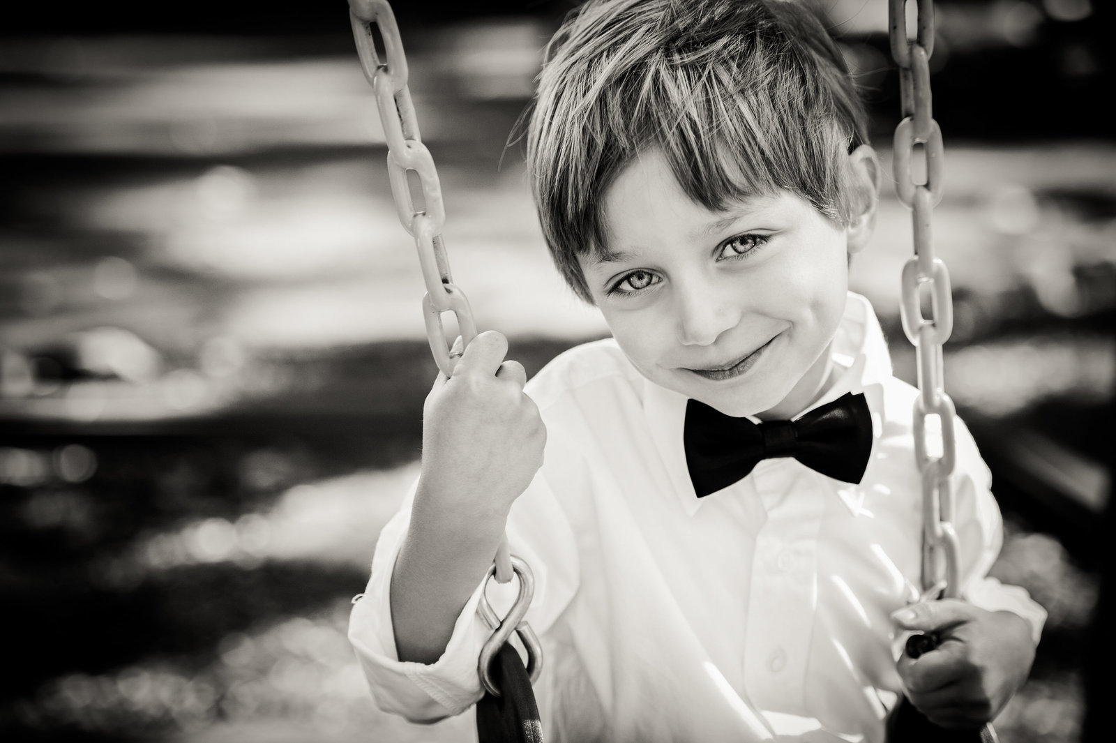 black and white of boy on swing with bow tie