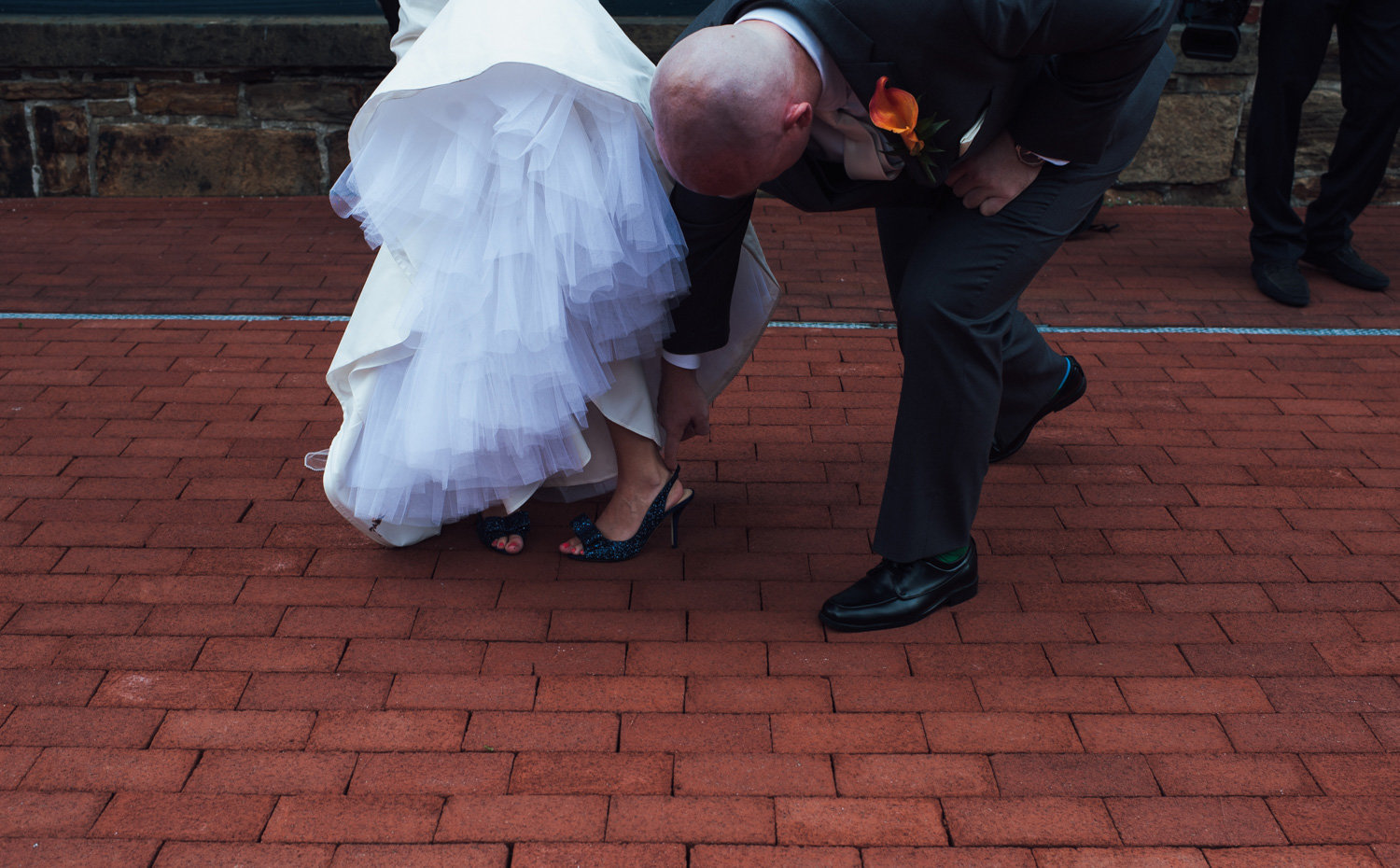 Groom fixes bride's blue shoes outside Phoenixville Foundry.