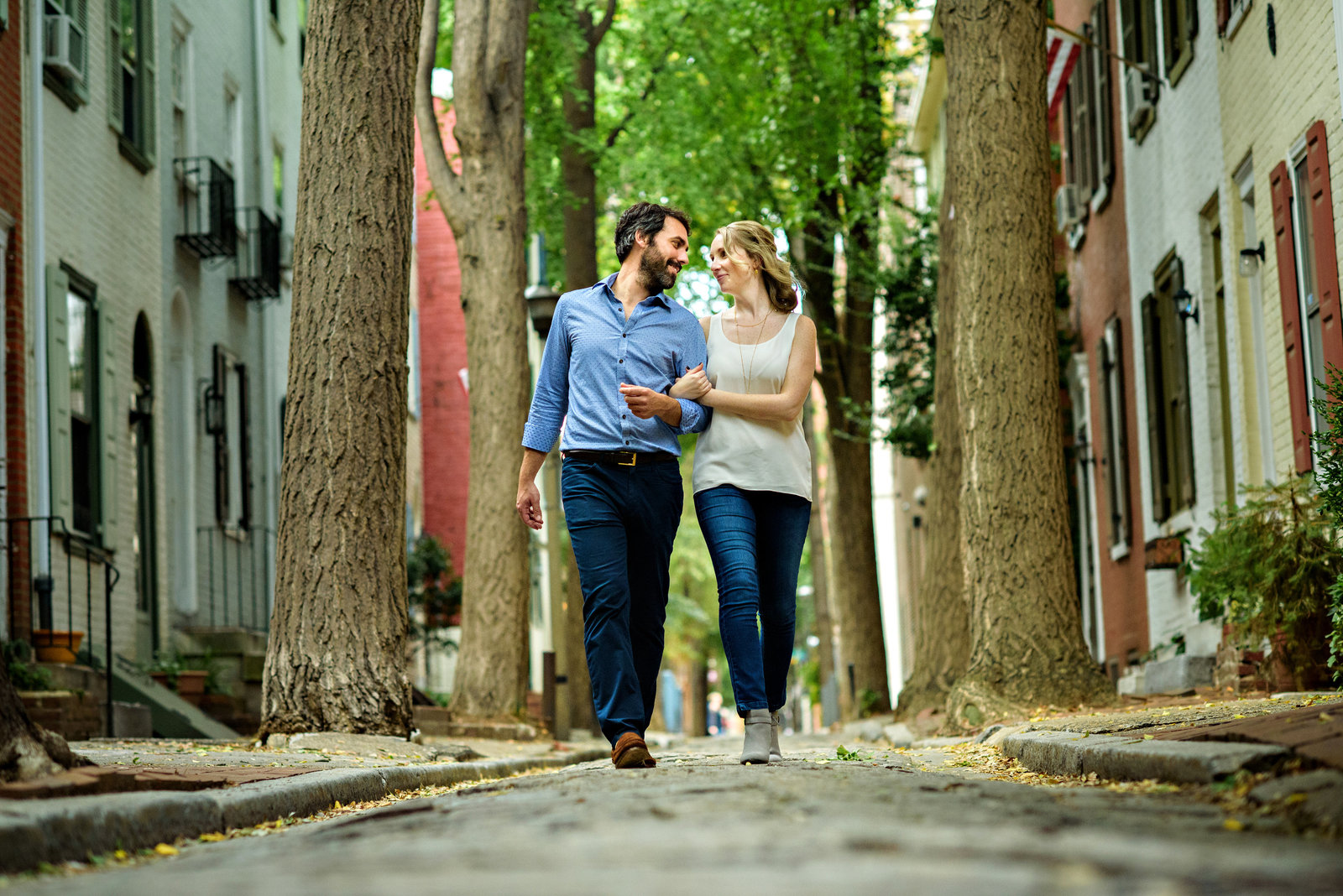 A fun couple walk the cobblestone streets of center city philly.