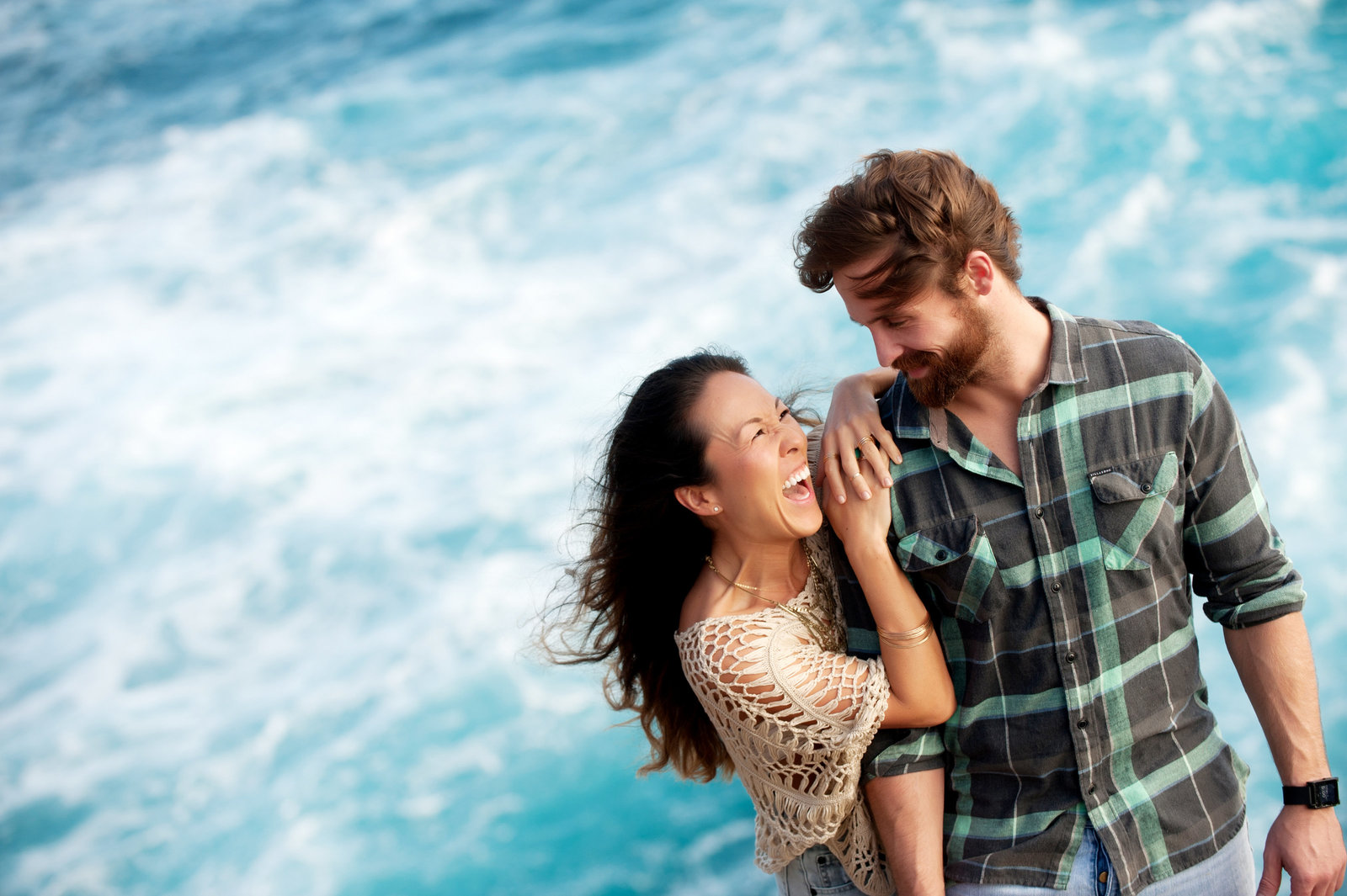 a couple laugh in front of bright blue water in honolulu