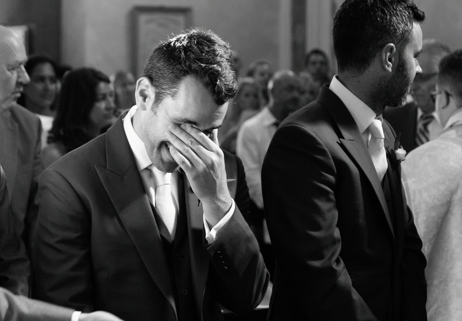 Excellent black and white documentary wedding photo by Adorlee of the best man cracking up into laughter during the ceremony at this destination Church wedding in Tuscany, Italy